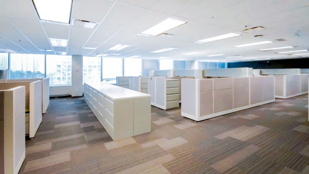 Interior photo of the office with white cubicles and file cabinets