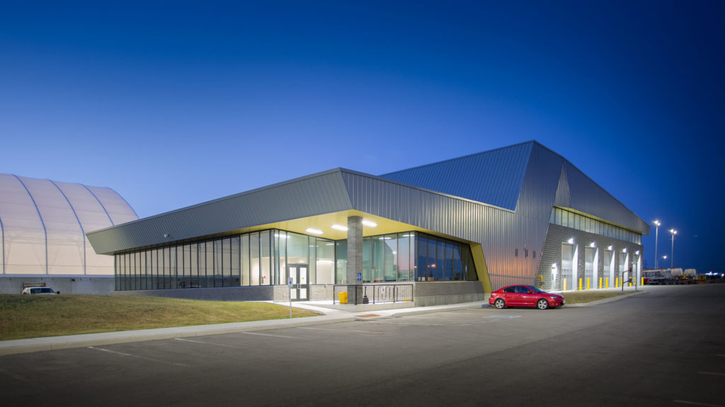 Exterior night photo of the facility with the parking lot in the front