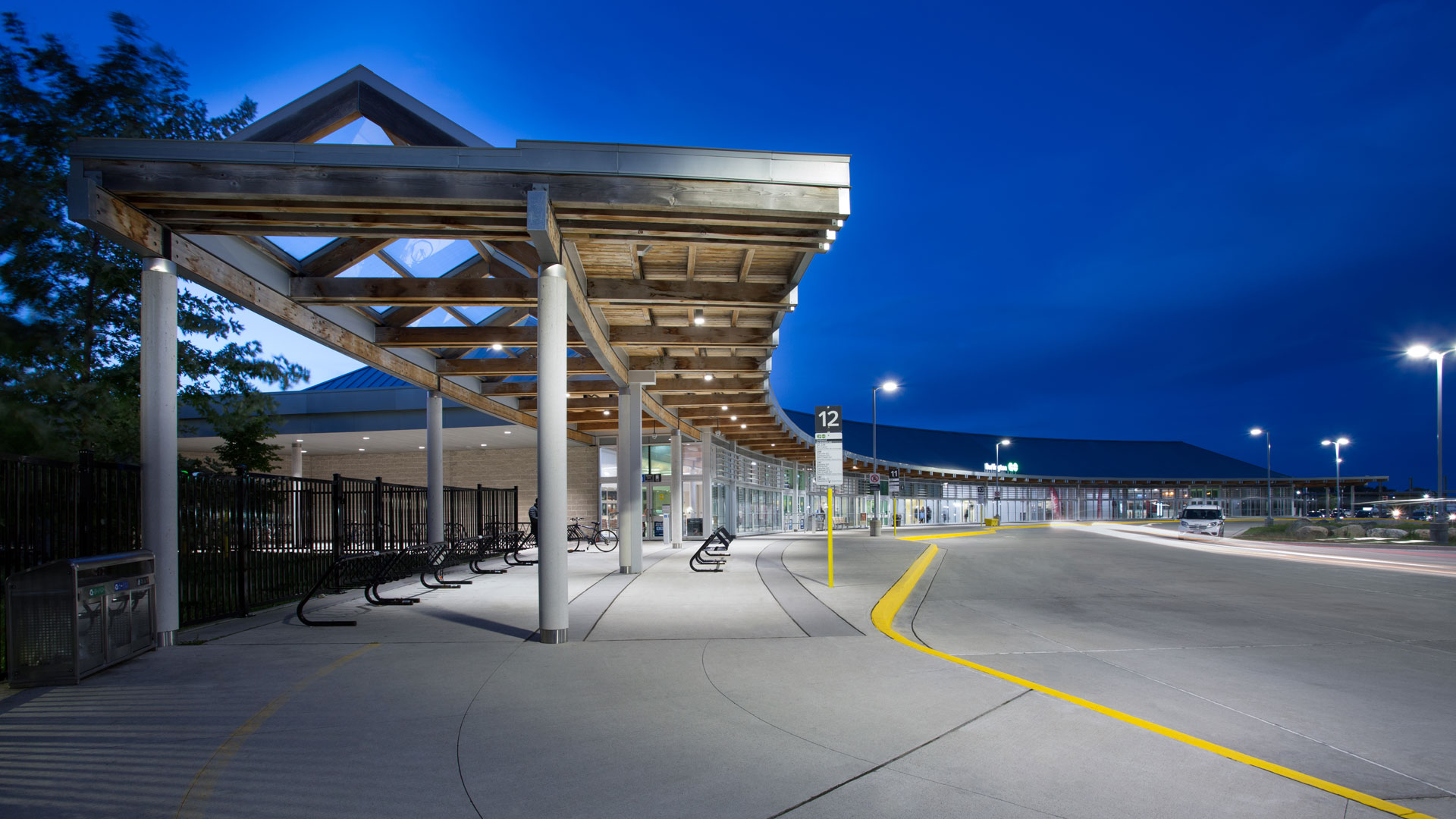 Exterior photo of the facility at night, showing the bike storage area