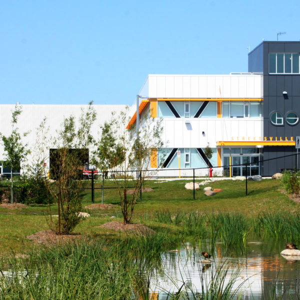 Exterior photo of the facility showing the building, landscape and a pond