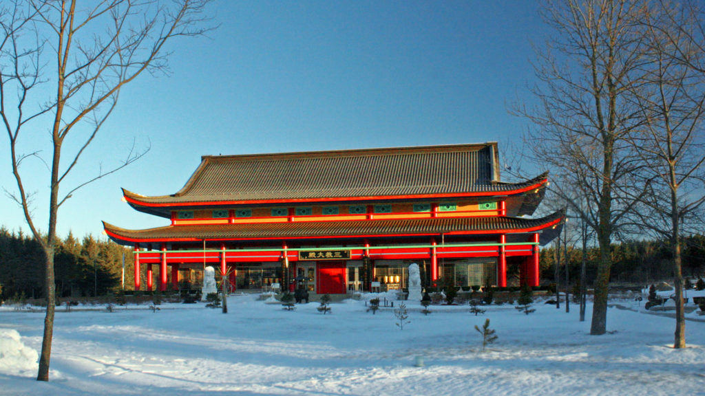 Exterior photo of the temple in winter surrounded by woods