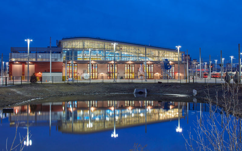 Exterior night photo of the facility in front of the storm water management pond