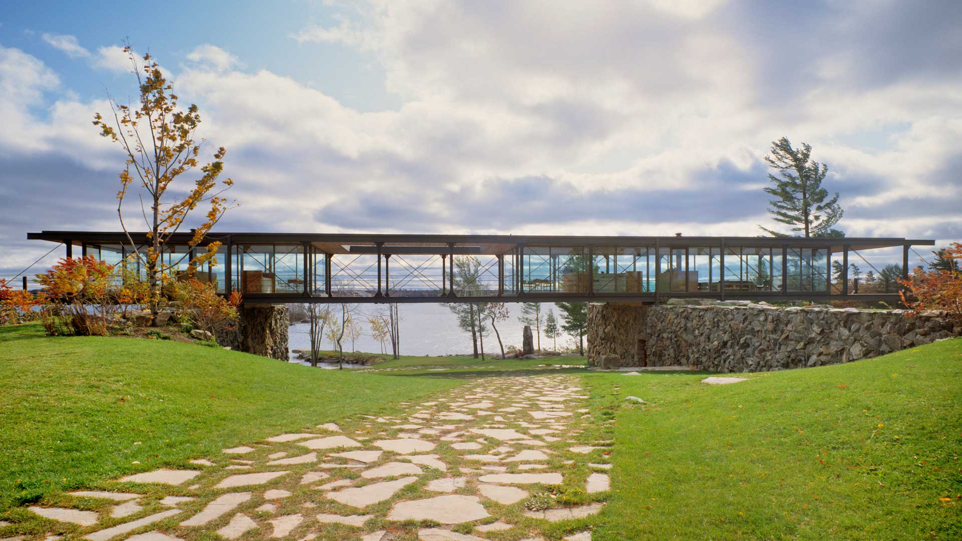 Exterior photo showing the residence in entirety surrounded by grassland and the lake in the back