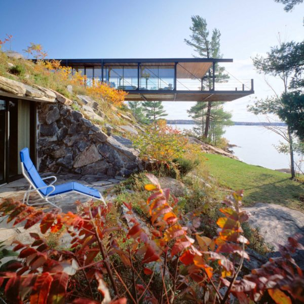 Exterior photo of the cantilevered structure, patio and landscape in the front, lake in the back