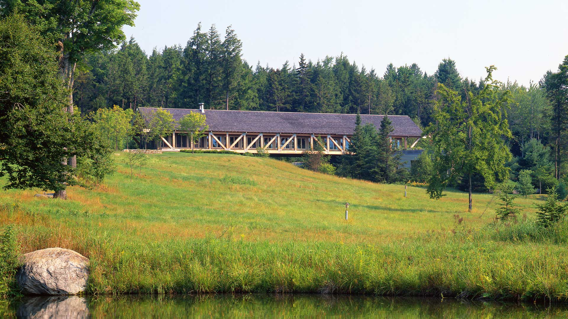 Exterior photo showing the entire bridge building, the pond and grassland in the front, and woods in the back